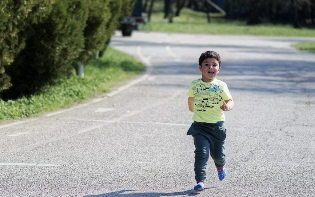 Little boy running on greenbelt - YMCA fun run St. Patrick's Day in Boise